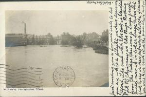 """The writer of this postcard wrote the following: """"Just sending you a few postcards to let you see what a plight we have been in Ilford. This view is the River Roding from the bridge. This was a large green field now it is like a large river but glad to say it has subsided a little of course. You will have read it in the papers I have sent you."""""""